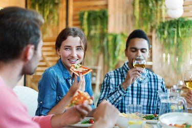 Group of joyful young friends enjoying talking, eating pizza and drinking wine during dinner in Italian restaurant