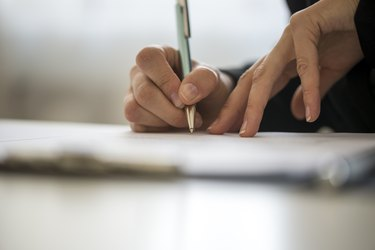 Hands of a person writing on a notepad