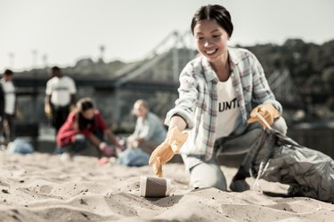 Smiling socially active woman wearing gloves gather empty coffee cups on beach