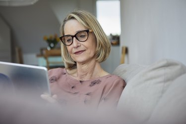 Mature woman at home using tablet on the sofa
