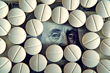 Out of Pocket Vs. Annual Deductible          Tablets on dollar bills (treatment, addiction, aging - concept).