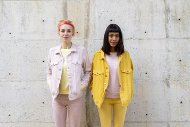 Two alternative friends having fun, wearing yellow and pink jeans clothes