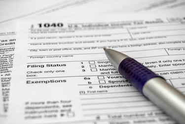 How to Meet the IRS Definition of a DependentTax form with pen