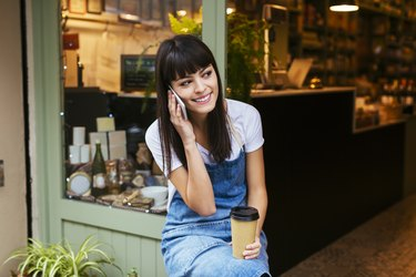 Smiling woman sitting at entrance door of a store talking on cell phone