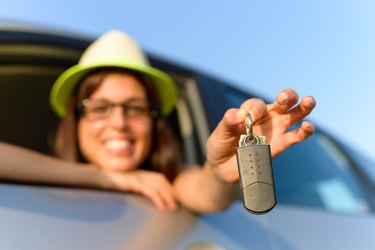 How to Buy a Repossessed Car                       Woman holding car keys
