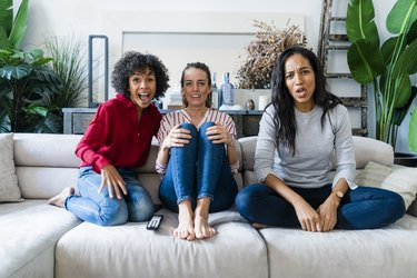 Three excited women on couch at home watching Tv