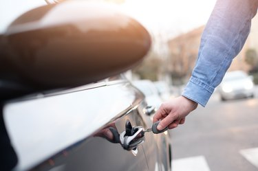 Hand holding a car key and opening the car door