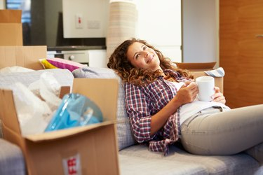 How to Move Out of Your Parent's House - Quick!Woman relaxing on couch surrounded by moving boxes