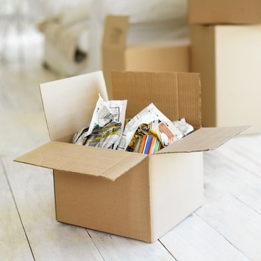 How to Evict a Roommate in California             Open cardboard box with objects wrapped in newspaper