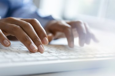 Hands of young woman typing on computer keyboard