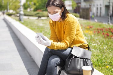 Young Woman With Face Mask Using Smart Phone drinking coffee in city