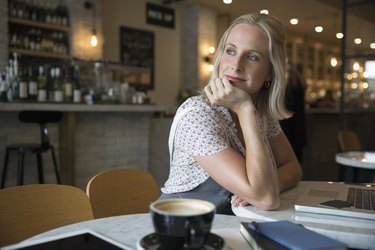 Smiling pensive woman using laptop, looking over shoulder in cafe