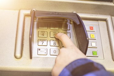 Close-up of hand entering PIN on ATM, bank machine keypad