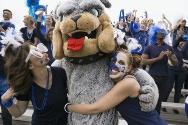 Fans hugging bulldog mascot in bleachers sports event