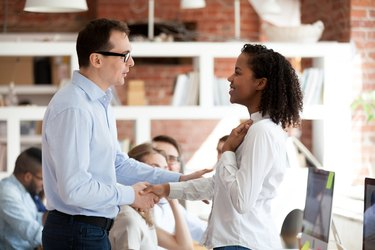 Executive team leader handshaking excited proud african employee, rewarding concept
