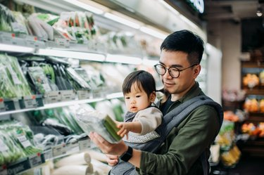 Young Asian father with cute little daughter grocery shopping for fresh organic vegetables in supermarket