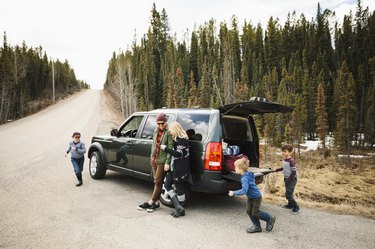 Family standing and playing outside SUV at remote roadside