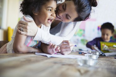 Affectionate, happy mother hugging toddler daughter coloring at table