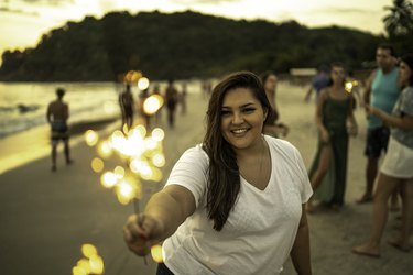 Young woman celebrating New Year with sparkler at beach