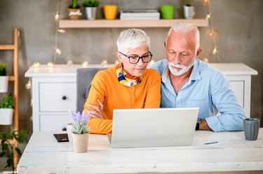 Mature grey senior couple shopping online during pandemic Covid-19 . Corona virus.
