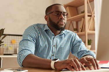 Busy day. Smart young afro american man in glasses working on the computer while sitting at his working place at home. Afro american businessman working remotely at home