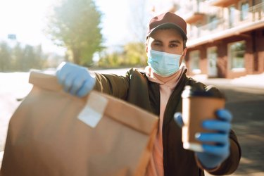 Courier in protective mask and medical gloves delivers takeaway food and coffee.