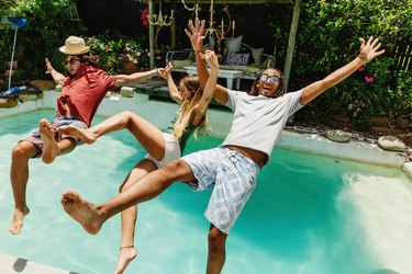 Three fully clothed friends falling backwards into pool