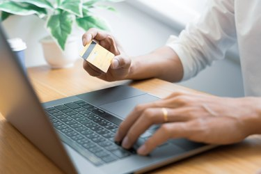 Man paying with credit card and entering security code for online shopping making a payment or purchasing goods on the internet with laptop computer, online shopping concept.