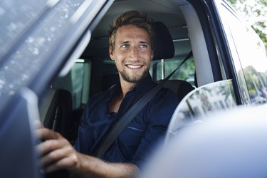 Smiling young man in car