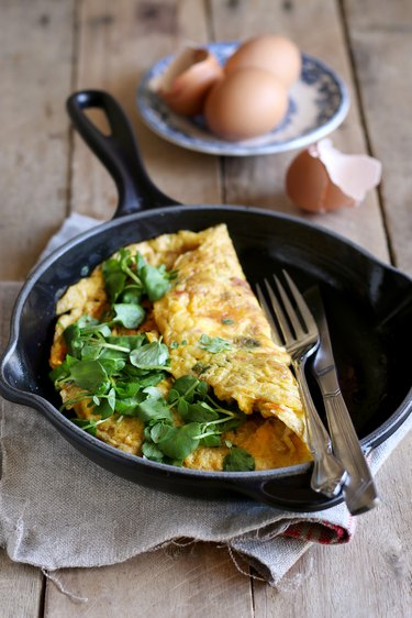 Homemade omelet with watercress on wooden background