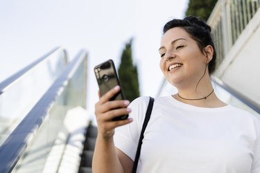 Smiling curvy young woman using mobile phone on escalator