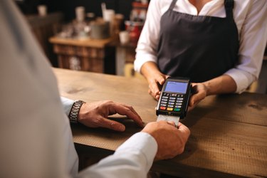 Customer doing payment of coffee by credit card at cafe