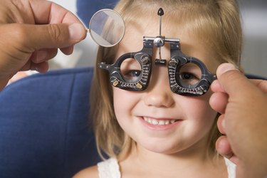 Optometrist giving young girl an eye examination