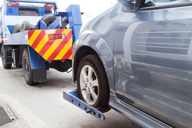 Car Repossession Laws in Michigan              Tow truck towing a broken down car on the street