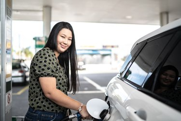 Portrait of young woman refueling her car at a gas station