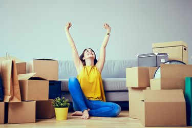 Happy young woman moving to new home - having fun