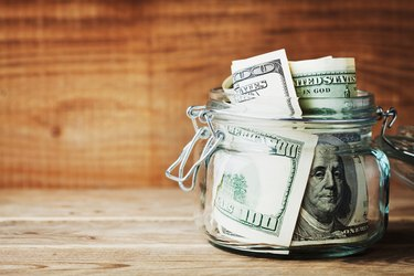 Dollar bills in glass jar. Saving money and finance concept.
