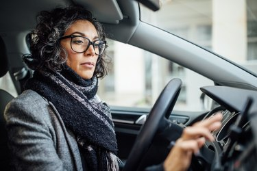 Woman behind the wheel using phone for navigation