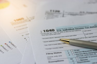 Selective focus a pen on US tax form 1040 on top for background / taxation concept