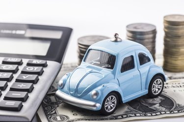 Close up blue car with calculator and coin.Selective focus in car.