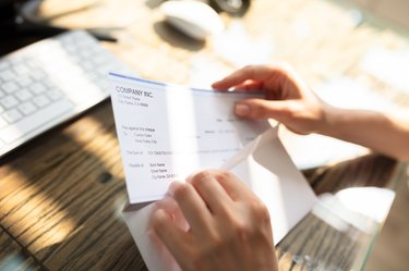 Businessperson Opening Envelope With Paycheck