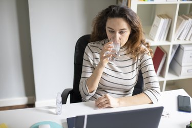 Freelancer young woman working at home and drinking water