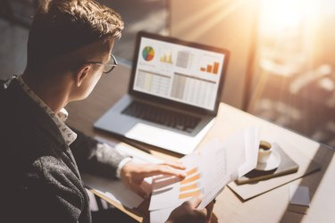 Young finance market analyst in eyeglasses working at sunny office on laptop while sitting at wooden table.Businessman analyze document in his hands.Graphs and diagramm on notebook screen.Blurred.