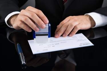 Businessman Stamping Cheque