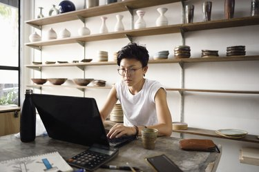 Young Asian entrepreneur working from her laptop in her store