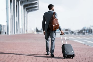 Businessman Going On Business Trip Arriving At Airport, Back View
