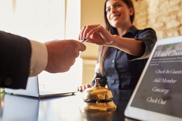 What Is a Pre-Authorization for a Settlement Credit?Guest takes room key card at check-in desk of hotel