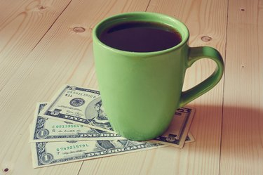 Cup of coffee on dollar bills pile