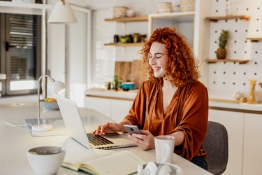 Young redhead woman is working from home