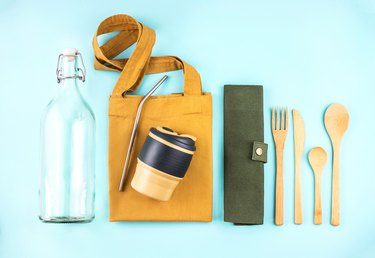 Eco bags with bamboo cutlery, reusable coffee mug and water bottle.
